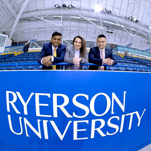 Three students in front of Ryerson banner